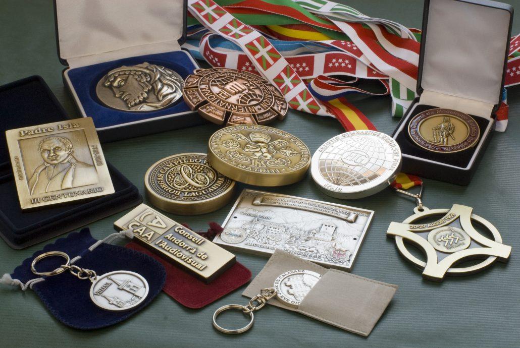 Bodegón de Medallas, Estuches, Llaveros, Fundas, Pisapapeles y Cintas.